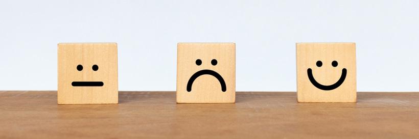 3 smileys sur une table symbolisant l'augmentation de la satisfaction client