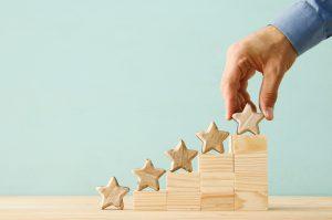 main masculine qui met une 5ème étoile en bois sur un escalier, symbole de la satisfaction client qui augmente