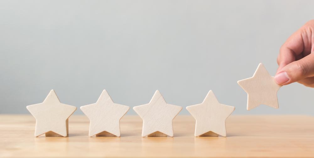 5 étoiles en bois alignées sur une thème symbolisant la satisfaction client qui augmente