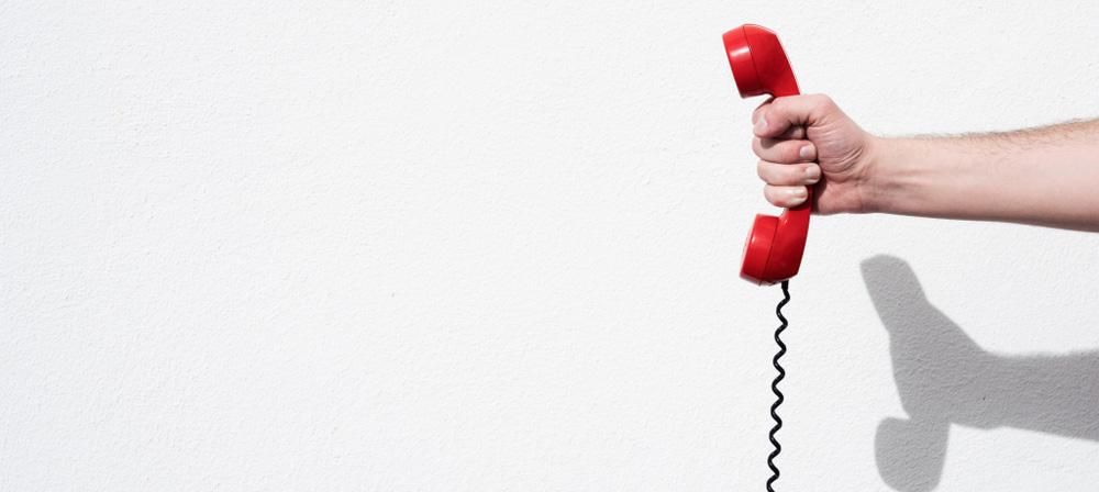 main tenant un téléphone rouge, symbole du mystery shopping par téléphone