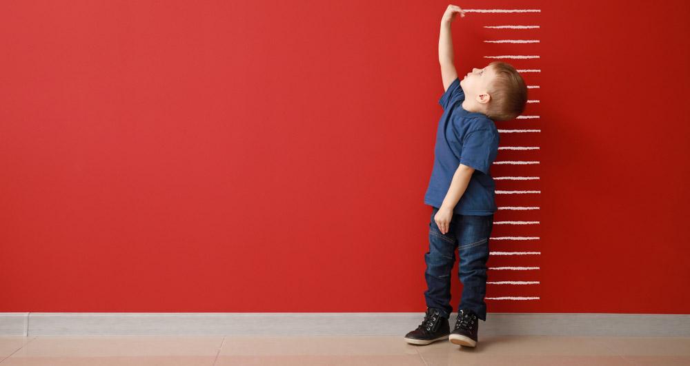 petit garàon en train de se mesurer devant un mur rouge